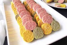 Horizontal image of two rows of neatly stacked colored cookies on a white dish.