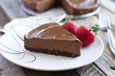 Horizontal image of a slice of a creamy chocolate torte on a white plate next to two whole strawberries.
