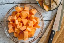 Closely cropped top-down image of a large glass bowl of orange cantaloupe chunks beside a wooden cutting board and a chef