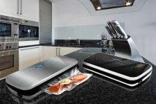 The NutriChef PKVS18SL Compact Vacuum Sealer sitting on a granite coutnertop in a higher end kitchen.