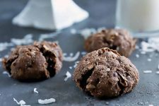 Horizontal image of three round mounded chocolate cookies with cracks in the outside, on a gray slate surface with scattered pieces of coconut, with a white ceramic pedestal cake server and a glass bottle of milk in the background.