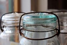 Three old glass mason jars on windowsill with rusty tops.