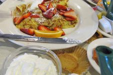 A plate of pancakes and a bowl of whipped cream on a table with packets of butter, a muffin wrapper, and other breakfast items, at Omega Restaurant in Illinois.