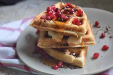 Horizontal image of three quartered waffles on a white plate garnished with pomegranate seeds and maple syrup.