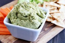 Horizontal image of a dish with kale and basil hummus surrounded by pita chips and fresh crudite.