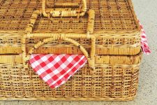 A picnic basket with checkered blanket peaking out.