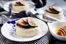 Horizontal image of three plates with panna cotta garnished with figs next to a bowl of honey and metal forks.