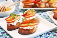 Three peach and basil crostini with ricotta on a square white plate, with twomore plates in the background, and a small round dish of honey with a wooden dipper, on a table topped with a dark and light blue cloth.
