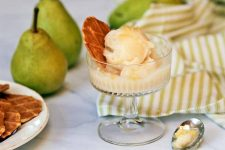 A glass parfait dish slightly right of center of the frame holds two scoops of pears sorbet and a cookie garnish, on a marble surface with a gathered green and white striped cloth, whole fruit, a white plate of cookies, and a spoon.