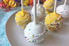 Horizontal image of yellow and white treats on sticks with decorations.