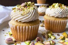 Horizontal close-up image of yellow cupcakes in white liners decorated with thick white frosting topped with pistachios.