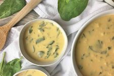 Horizontal image of three bowls of creamy potage on a white towel with fresh spinach leaves and a wooden spoon.
