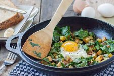 A cast iron wok hold a potato and been green hash sitting on a checkered blue and white folded table cloth.