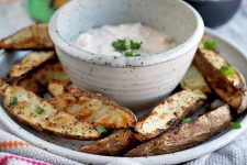 Horizontal image of a bowl of a creamy condiment on a plate with grilled spuds.