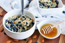 Horizontal image of one round ceramic bowl in the foreground and a square bowl in the background, filled with a mixture of quinoa, fresh blueberries, chopped almonds, and cinnamon, with a spoon stuck into the closer bowl, with a small white dish of honey with a wooden dipper for serving to the right, on a white gathered cloth on top of a brown wood surface, with scattered whole nuts and berries.