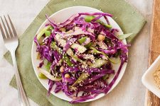 Top view of a plate of purple cabbage and shaved asparagus slaw.
