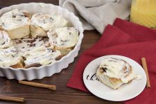 Cinnamon roll with ream cheese glaze on a small white plate, beside a white fluted ceramic dish of more sweet buns, on a brown wooden table with white and red cloths and scattered cinnamon sticks.