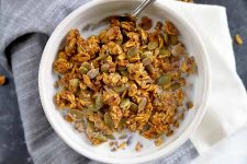 Horizontal overhead image of a white ceramic bowl of homemade pumpkin spice granola and milk, on a white cloth to the right and a gray striped cloth to the left, on a gray surface.