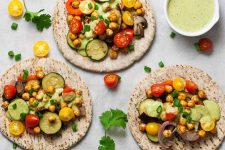Three pieces of pita bread with roasted and fresh vegetables and garbanzo beans on top, with a small white ceramic dish of a pale green sauce, and scattered red and yellow cherry tomatoes and green cilantro leaves, on a white piece of parchment paper.