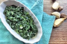 Horizontal overhead image of an oblong fluted white ceramic serving dish of creamed collard greens, on a folded blue-green cloth, on a wood surface with whole nutmeg and cloves of garlic to the right.