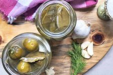 Horizontal overhead image of two jars of pickles with brine and bay leaves, on a wood cutting board with a red and white checkered cloth with fringe, with garlic, salt, and dill, on a gray background.