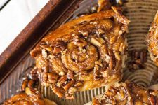 Closeup of a pecan sticky roll on a brown metal baking sheet.