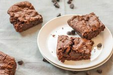 Two brownies on a white dessert plate, with two more to the left on a gray linen tablecloth, with scattered dark chocolate chips.