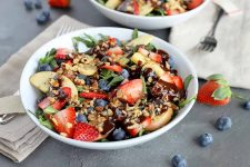 Horizontal image of a shallow white ceramic bowl of arugula topped with fresh fruit, chopped nuts, and chocolate balsamic vinaigrette, on a gray surface with two folded beige cloth napkins, forks, and scattered berries, with another bowl of the same dish at the top of the frame.