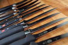Close up of 12 different boning knives on a maple cutting board diffused focus | Foodal