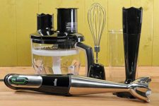 The Braun MQ777 Multiquick Hand Blender Set with accessories on a maple wooden table and green wooden background.