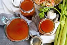 Horizontal image of jars and cups of a red liquid next to fresh vegetables.