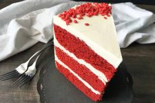 Horizontal image of a slice of red velvet cake on a gray stand.