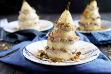 Horizontal image of a plated fruit and ricotta stack covered in nuts, with the same two plated desserts in the background on blue napkins.