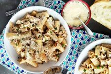 Horizontal top-down image of white bowls of a creamy pasta dish on a patterned blue towel next to a red bowl with grated cheese.