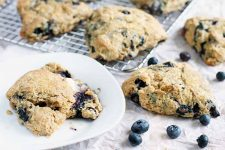 Blueberry scones on a white plate, a metal cooling rack, and a white piece of parchment paper, with a few scattered raw berries in the foreground.