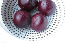 A close up view of four roasted beets in a white colander.