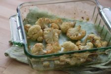 Roasted cauliflower in a baking pan still warm from the oven.