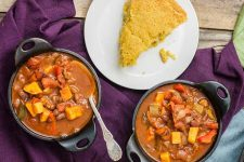 Top down view of two bowls of roasted four-pepper chili and a slice of cornbread on a wadded purple table cloth.