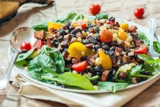 A large white plate topped with a base layer of spinach, topped with black beans, red and yellow halved grape tomatoes, grilled corn kernels, and chopped roasted orange sweet potato, with a round serving spoon, on a white folded napkin, on top of a table spread with a large brown piece of craft paper.
