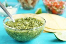 A clear glass dish of green salsa verde with a spoon, with tortillas, lime wedges, a dish of onions, and a dish of pico de gallo in soft focus in the background.