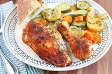 Roasted spiced chicken breast and a drumstick on a dinner plate with squash and root vegetables, and a piece of bread, beside silverware on a blue and white cloth napkin, on a brown wood table.