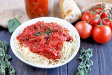 Horizontal image of a white shallow bowl of cooked spaghetti topped with marinara, on a brown wood table with tomatoes on the vine, a piece of baguette, a jar of sauce, and sprigs of basil and oregano, with a piece of burlap in the background.
