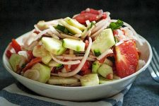 A white porcelain bowl full of Simple Summer Tomato Cucumber Salad.