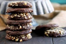A stack of walnut-coated chocolate cookies on a dark brown wood surface, to the left of a few more on soft focus to the right, with a ceramic cake stand and a piece of burlap in the background.