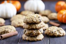 Horizontal image of four cookies stacked on top of one another with orange and white pumpkins and more desserts in the background.