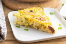 Horizontal image of a slice of an egg bake with sausage crumbles, potatoes, and scallion slices.