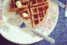 A top view image of a half-eaten Belgian waffle on a plate with a fork and knife beside it.
