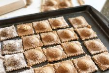 Horizontal image of a baking sheet with rows of a filled square pasta.