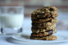 A stack of delicious looking dark cookies on a white plate and glass of milk at the back.
