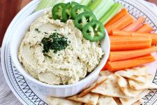 Horizontal image of hummus garnished with jalapeno and cilantro, on a platter with celery, carrots, and pita triangles.
